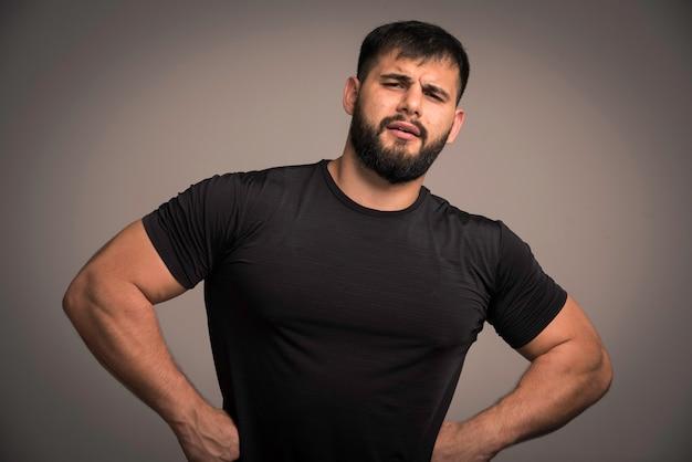 Sportieve man in zwart shirt kijkt aarzelend.