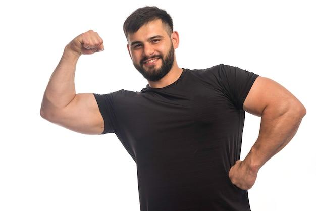 Sportieve man in zwart shirt met een sterk gevoel