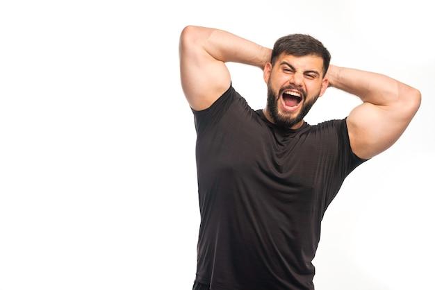 Sportieve man in zwart shirt met zijn triceps en schreeuwen.