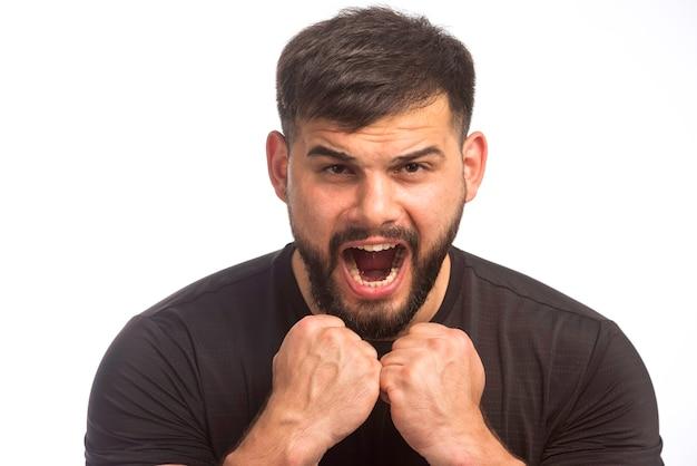 Sportieve man in zwart shirt met zijn vuisten.