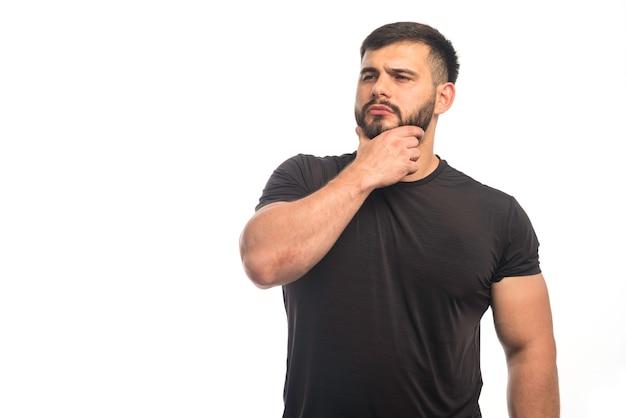 Sportieve man in zwart shirt zijn hand op zijn baard.