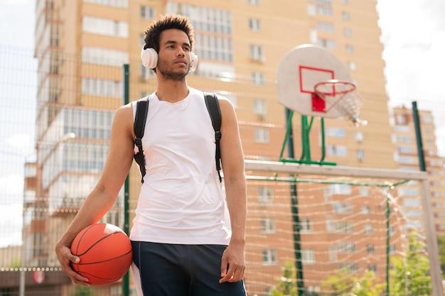 Sportieve man met bal voor het spelen van basketbal, luisteren naar muziek in koptelefoon op speelplaats van veld