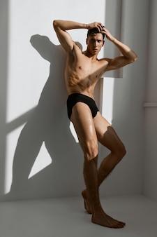 Sportieve man met een gespierd lichaam in zwarte slipje poseren bij het raam