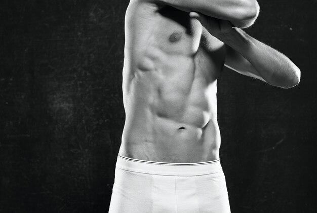 Sportieve man met een opgepompt lichaam donkere achtergrond