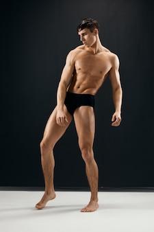 Sportieve man met gespierd lichaam in zwarte slipje poseren tegen een donkere achtergrond