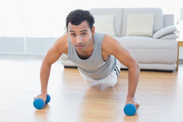 Sportieve man met halters doen push-ups in de woonkamer