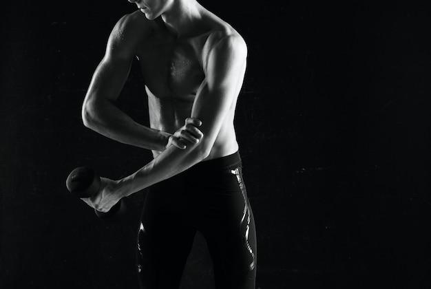 Sportieve man met halters in handen die spieren oppompen, oefeningen donkere achtergrond