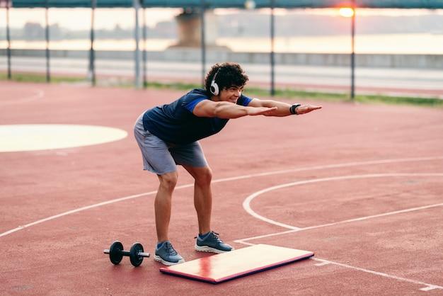 Sportieve man met krullend haar doen oefeningen op het veld en met koptelefoon in de oren. zomer in de ochtend.