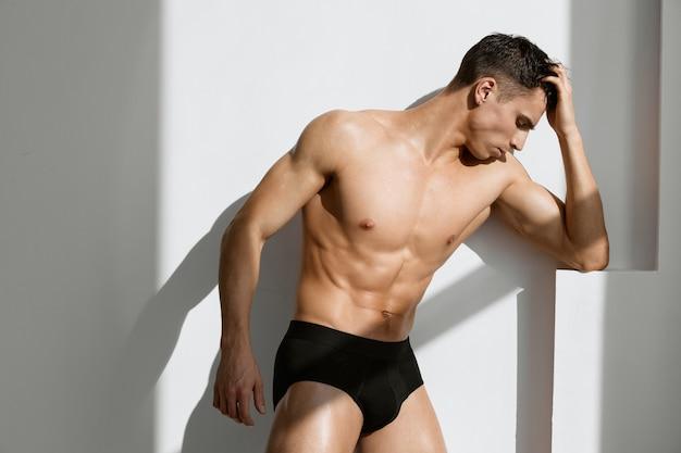 Sportieve man met naakt gespierd lichaam zwart slipje poseren