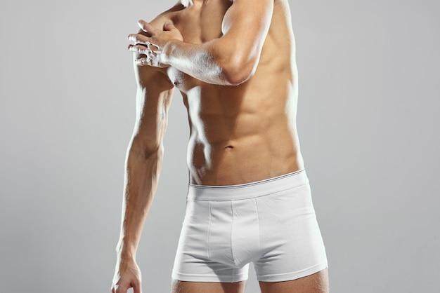 Sportieve man met opgepompt gespierd lichaam in witte korte broek workout lichte achtergrond