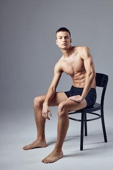 Sportieve man met opgepompt gespierd lichaam zittend op stoel fitness.