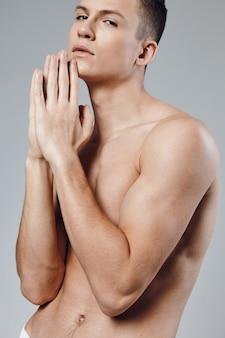 Sportieve man met opgepompte spieren van zijn handen verbond zijn vingers bij het gezicht