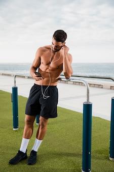 Sportieve man muziek luisteren voordat oefenen