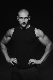 Sportieve man poseren in de studio op de achtergrond. sport, schoonheid, zwart-witfotografie