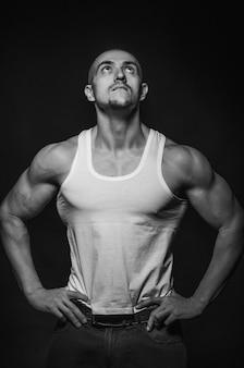 Sportieve man poseren in de studio op de achtergrond. sport, schoonheid, zwart-witfotografie.