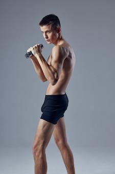 Sportieve man poseren in zwarte korte broek met halters in handen workout fitness geïsoleerde achtergrond