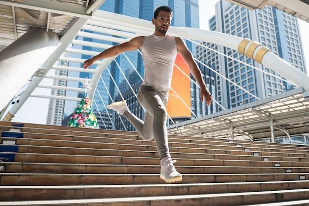 Sportieve man rennen en springen in de stad