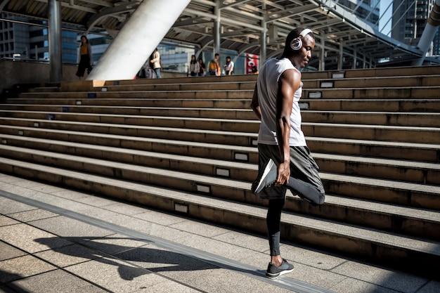 Sportieve man strekt benen en luistert naar muziek