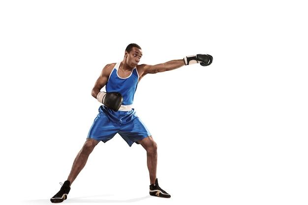 Sportieve man tijdens boksoefeningen hit maken. foto van bokser op witte achtergrond. kracht, aanval en bewegingsconcept. fit afro-amerikaanse model in beweging. afro gespierde atleet in sportuniform