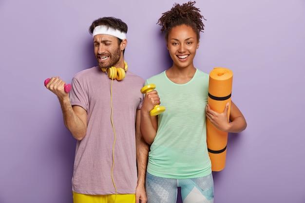 Sportieve man tilt zware halter op, werkt aan spieren