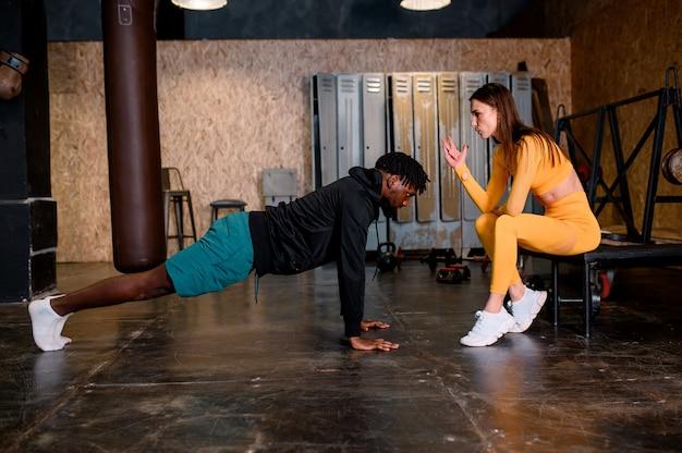 Sportieve man van gemengd ras met zijn meisje die oefening doet. multi etnisch paar. hoge kwaliteit foto