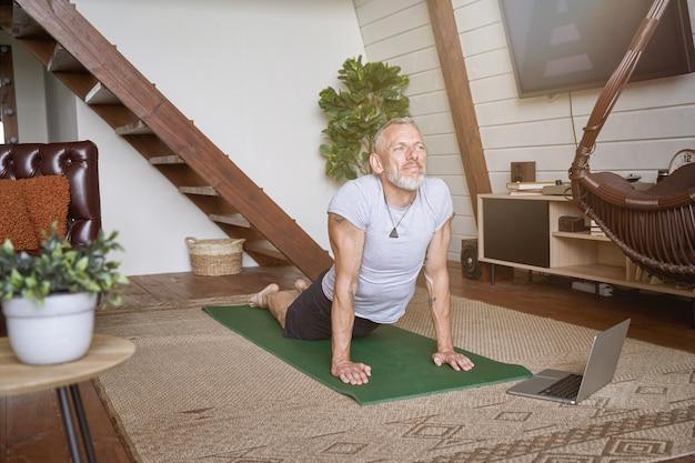 Sportieve man van middelbare leeftijd die thuis yoga-oefeningen doet in de woonkamer terwijl hij naar online les kijkt