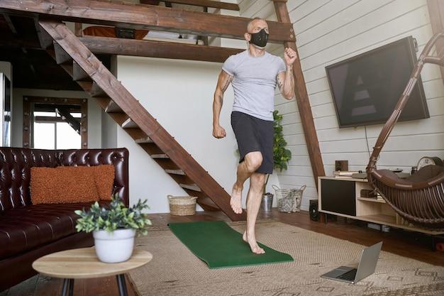Sportieve man van middelbare leeftijd met een gezichtsbeschermend masker die tijdens het kijken in zelfisolatie traint