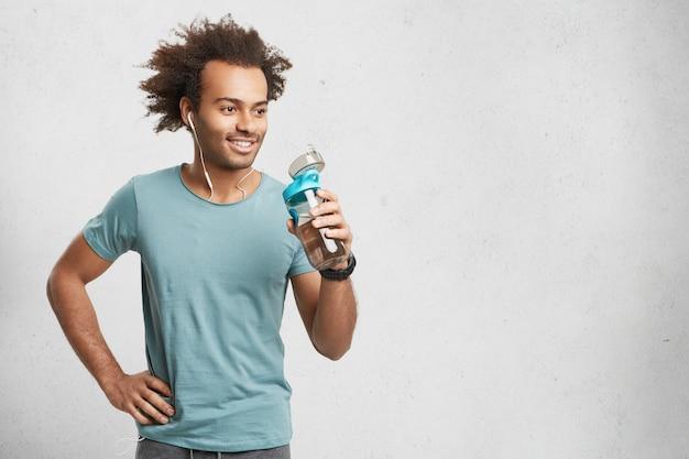 Sportieve mannelijke atleet heeft dorst na het hardlopen van lange afstanden
