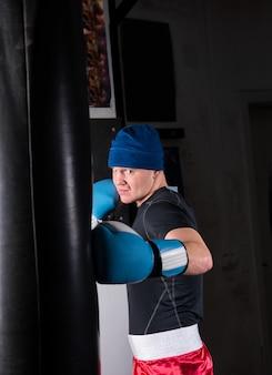 Sportieve mannelijke bokser in bokshandschoenen training met bokszak boksen in een sportschool