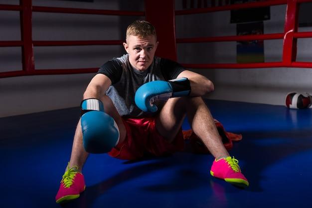 Sportieve mannelijke bokser in bokshandschoenen zitten in regelmatige boksring in een sportschool Premium Foto