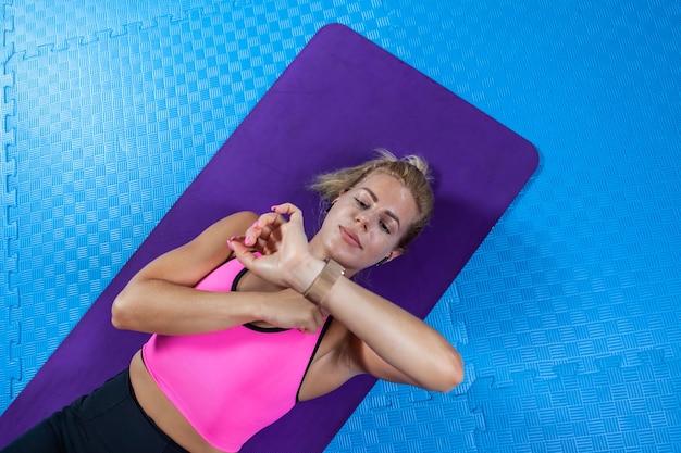 Sportieve mensen, gezonde levensstijl. jonge actieve vrouw met slank lichaam ontspannen na abdominale crunches oefening op yogamat en kijkt naar horloge in fitnessles.