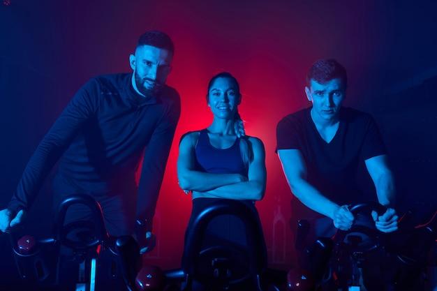 Sportieve mensen staan achter de fiets in de sportschool en kijken naar camera poseren, in trainingspakken
