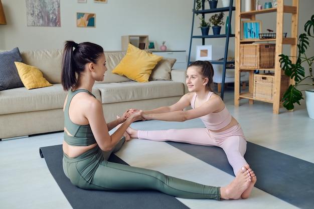 Sportieve moeder van middelbare leeftijd zit met uitgestrekte benen en trekt dochters handen terwijl ze haar helpt om thuis de benen te strekken