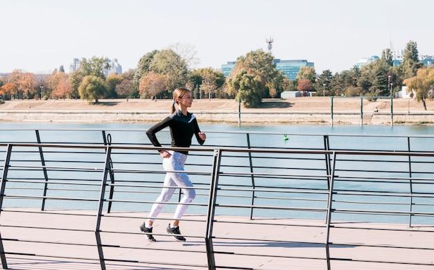 Sportieve mooie jonge vrouw die bij in openlucht loopt