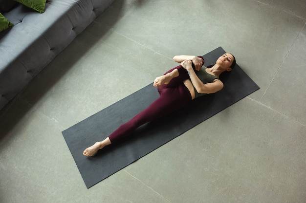 Sportieve mooie jonge vrouw die yoga-asana's als professional thuis beoefent.