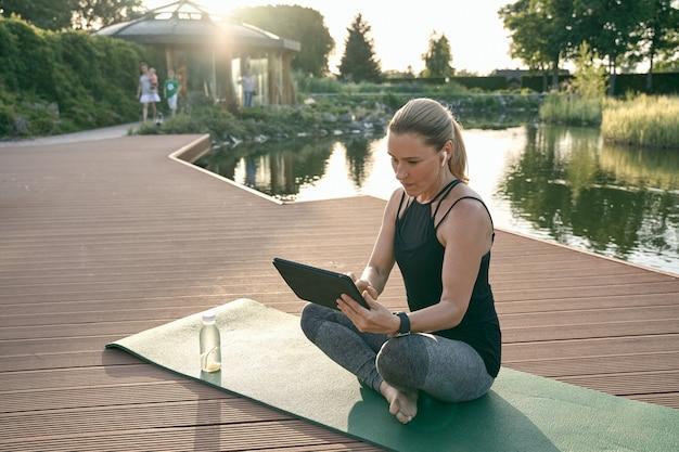 Sportieve mooie vrouw kijkt naar tutorial op een tablet-pc terwijl ze yoga doet op een mat in de natuur op een