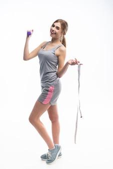 Sportieve mooie vrouw traint met een halter, toont het aan de camera en houdt een meetlint in haar hand.