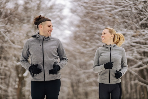 Sportieve paar samen uitgevoerd op besneeuwde winterdag in de natuur. buitenfitness, winterfitness, gezonde gewoonten