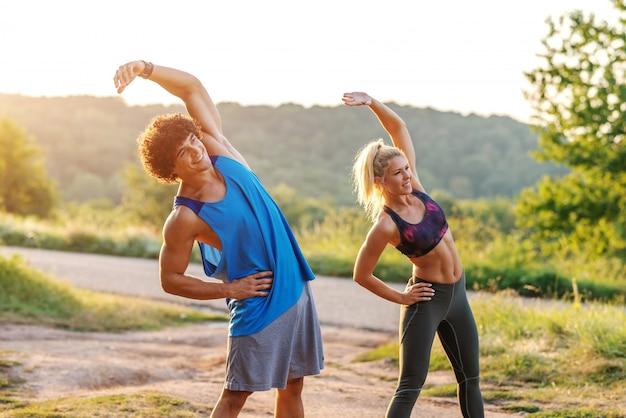 Sportieve prachtige kaukasische paar in sportkleding warming-up voor het hardlopen. zonnige zomerdag in de natuur. driekwart lengte.
