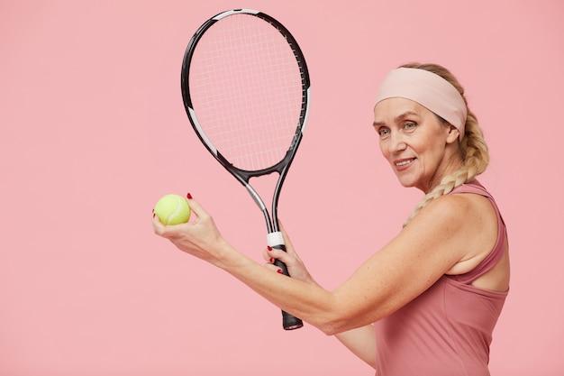 Sportieve rijpe het tennisracket van de vrouwenholding