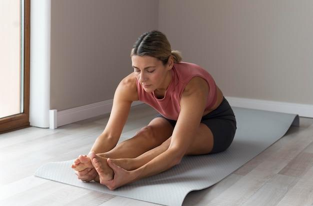 Sportieve rijpe vrouw met roze mouwloos onderhemd die trainingsoefeningen doet