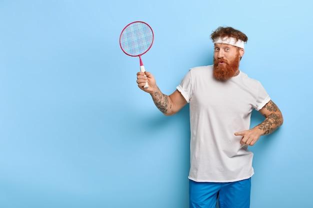 Sportieve roodharige tennisser houdt racket vast terwijl hij tegen de blauwe muur poseert
