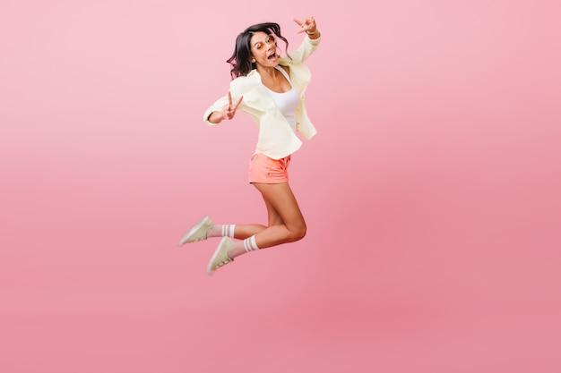 Sportieve sensuele latijns-meisje zwaaiende handen tijdens het springen. aantrekkelijk vrouwelijk model in vrijetijdskleding