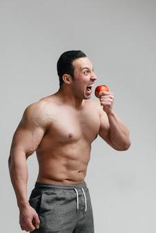 Sportieve sexy kerel die fruit op een witte achtergrond eet. eetpatroon. gezond dieet