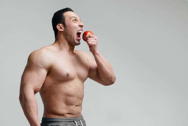 Sportieve sexy man fruit eten. eetpatroon. gezond dieet