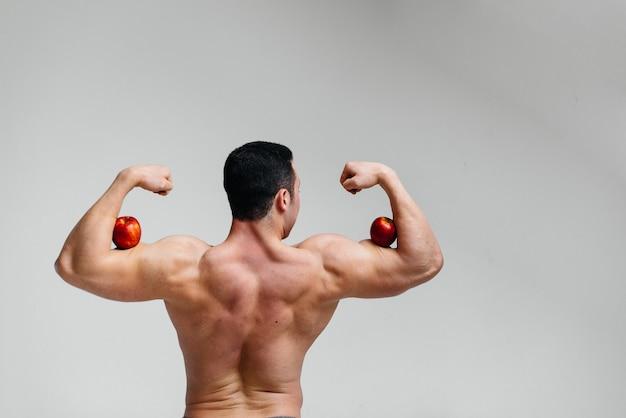 Sportieve sexy man poseren met heldere vruchten. eetpatroon. gezond dieet