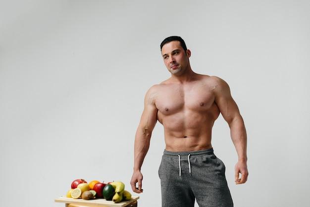Sportieve sexy man poseren met heldere vruchten. eetpatroon. gezond dieet.