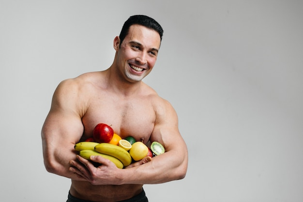 Sportieve sexy man poseren op een witte achtergrond met heldere vruchten. eetpatroon. gezond dieet