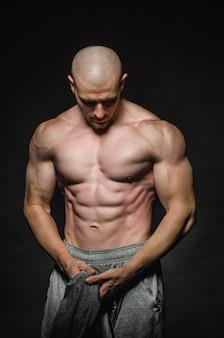 Sportieve sexy man staat topless op een donkere ruimte. sport, schoonheid.
