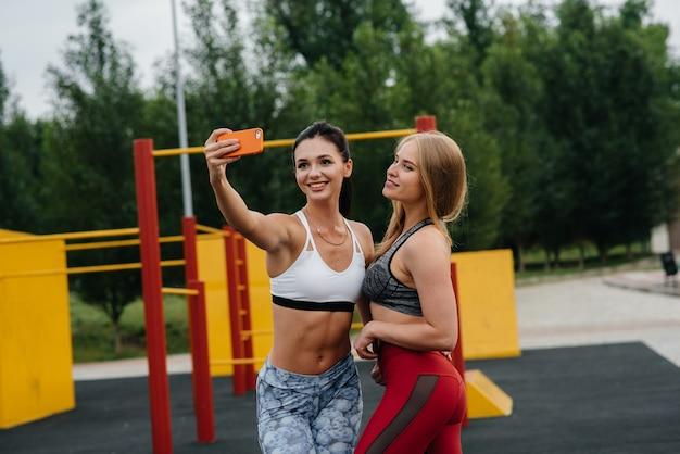 Sportieve, sexy meiden nemen selfies buitenshuis. fitness, gezonde levensstijl